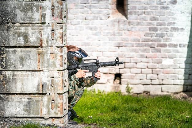 Kobieta w mundurze z bronią w wojskowym treningu paintballowym