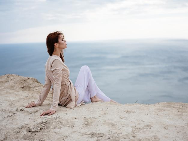 Kobieta w naturze w lekkim ubraniu siedzi na piasku i oceanu w tle