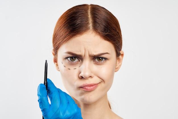 Kobieta w niebieskich rękawiczkach trzyma w rękach strzykawkę i wskazuje na twarz wstrzyknięcie botoksu
