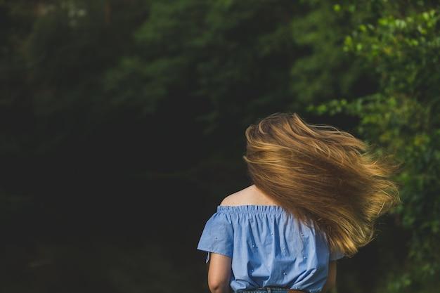 Kobieta w niebieskiej bluzce z długimi fruwającymi włosami na tle przyrody. pozytywne ludzkie emocje. długie włosy fruwające w ruchu. młoda kobieta tańczy w dzikiej leśnej naturze. dziewczyna podrzucając włosy z