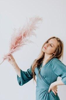 Kobieta w niebieskiej górze trzymająca różową trawę