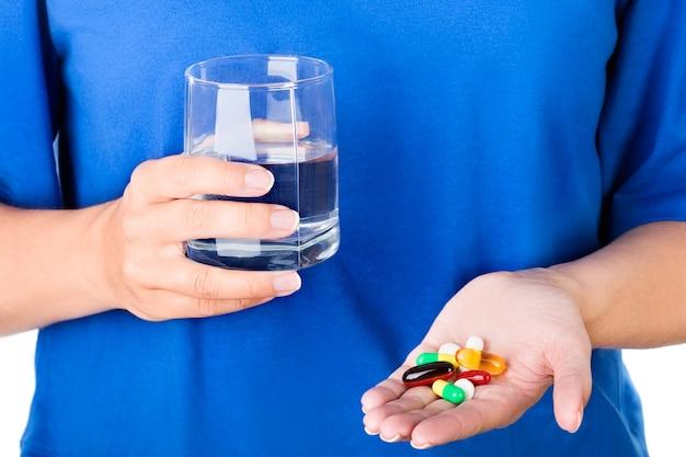 Kobieta w niebieskiej koszulce trzyma szklankę wody i opakowanie różnych kolorowych tabletek