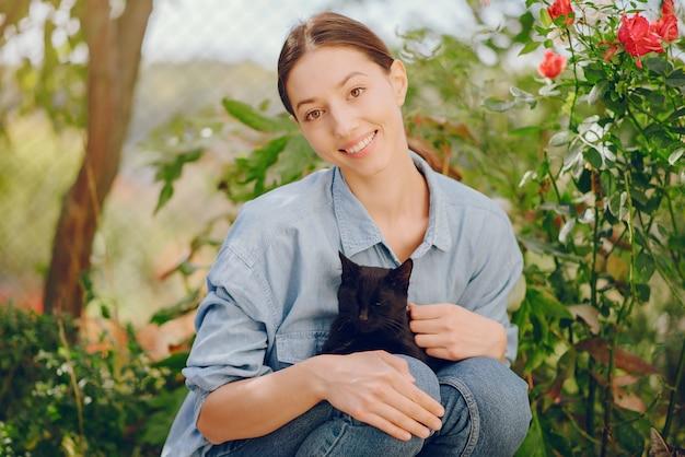 Kobieta w niebieskiej koszuli, grając z cute kitty