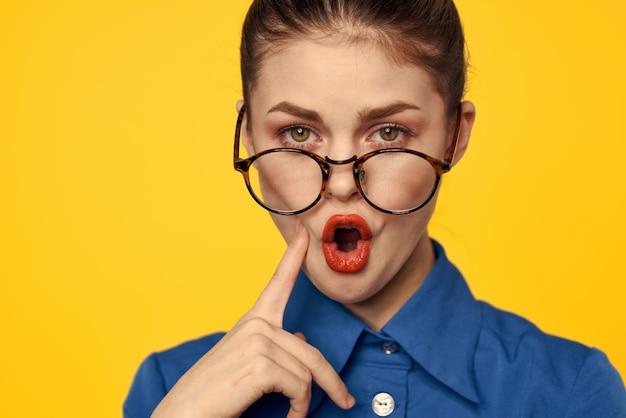 Kobieta w niebieskiej koszuli i okularach z jasnym makijażem gestykuluje