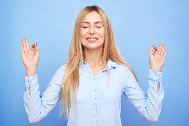 Kobieta w niebieskiej koszuli ma zamknięte oczy, trzymając palce w geście mudry, piękna dziewczyna menedżera zachowuje spokój relaksuje na białym tle na niebieskim tle, medytacja terapii antystresowej