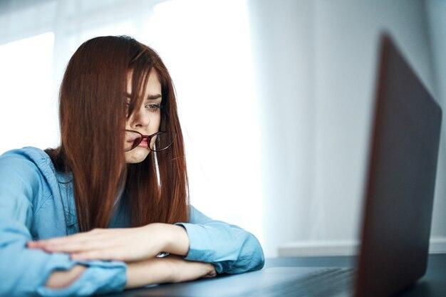 Kobieta w niebieskiej koszuli przed laptopem z depresją zmęczenia