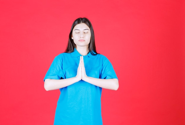 Kobieta w niebieskiej koszuli stojąc, łącząc ręce i modląc się.