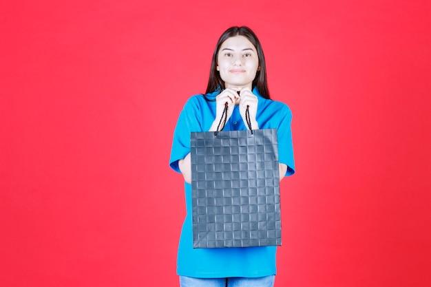 Kobieta w niebieskiej koszuli trzyma fioletową torbę na zakupy.