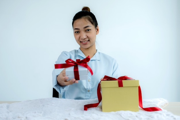 Kobieta w niebieskiej koszuli trzymająca białe pudełko zawiązane czerwoną wstążką prezent na święto dawania specjalnych świąt, takich jak boże narodzenie, walentynki