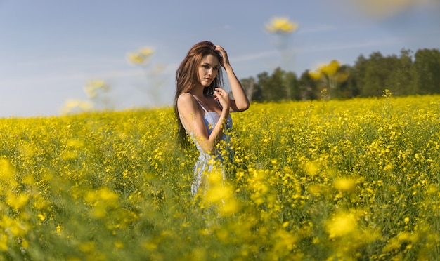 Kobieta w niebieskiej sukience idącej wzdłuż pola żółtych kwiatów w pogodny, słoneczny dzień