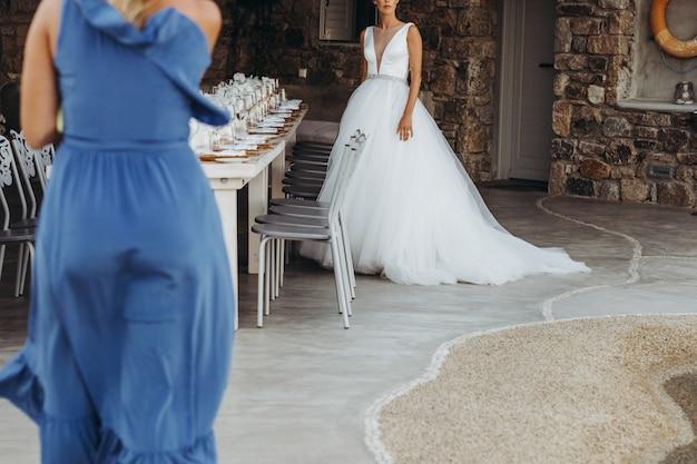 Kobieta w niebieskiej sukience idzie w kierunku panny młodej w eleganckiej sukni ślubnej