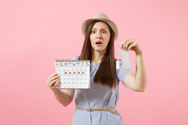 Kobieta w niebieskiej sukience, kapeluszu trzymając podpaskę, tampon żeński kalendarz okresów, sprawdzanie dni menstruacji na białym tle na różowym tle. medycyna, opieka zdrowotna, koncepcja wyboru ginekologicznego. skopiuj miejsce.