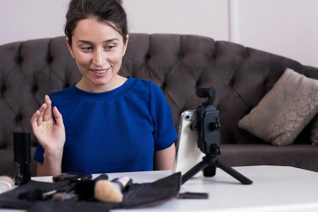 Kobieta w niebieskiej sukience prezentuje makijaż vlog