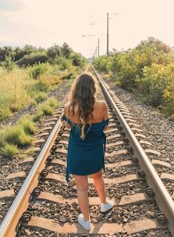 Kobieta w niebieskiej sukience spacerująca po torach kolejowych widok z tyłu