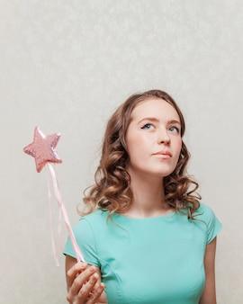 Kobieta w niebieskiej sukience trzyma gwiazdę na patyku