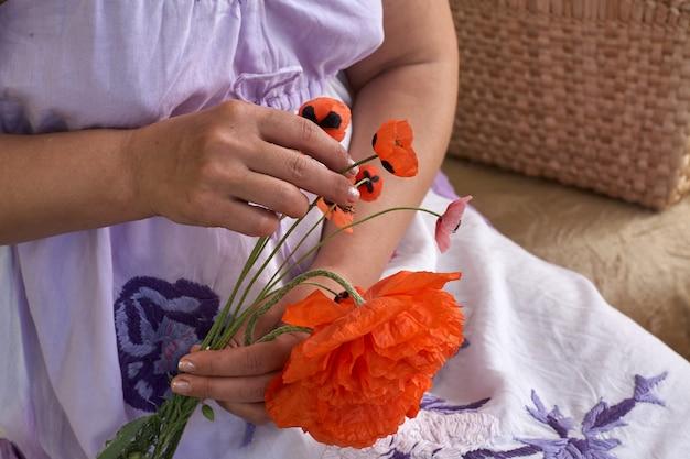 Kobieta w niebieskiej sukience trzyma kwiaty maku, z bliska na jej rękach. wiosenne sny.