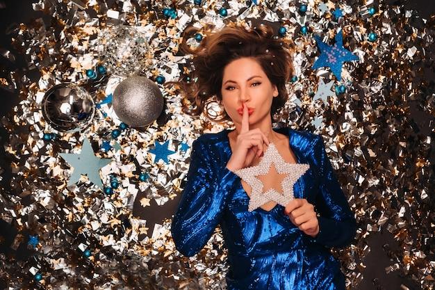 Kobieta w niebieskiej sukience z cekinami uśmiecha się i leży na podłodze pod spadającym wielobarwnym konfetti.