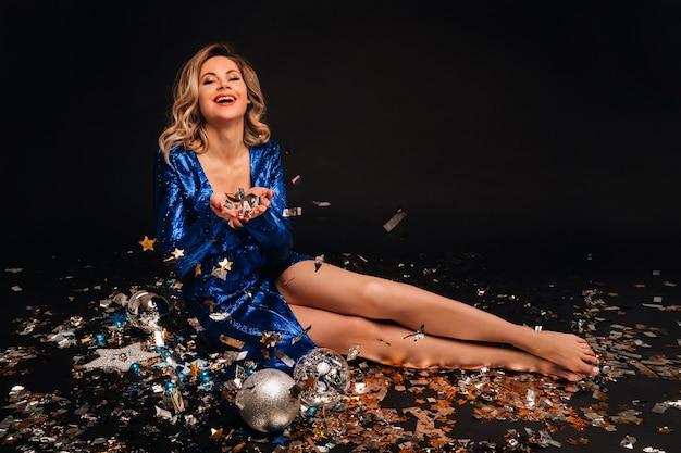 Kobieta w niebieskiej sukience z cekinami uśmiecha się siedząc na podłodze z konfetti na czarnym tle.