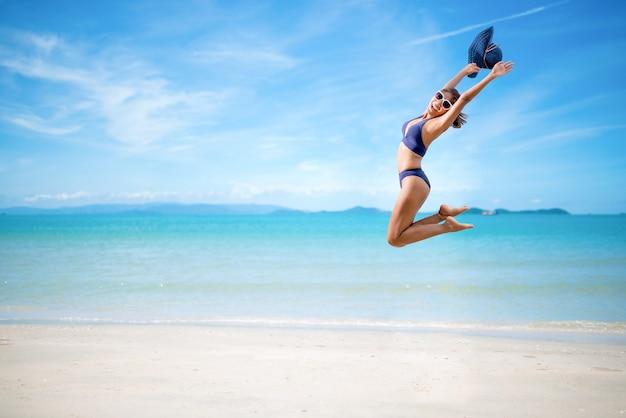 Kobieta w niebieskim bikini i kapeluszu przeciwsłonecznym skacząca po morskiej plaży