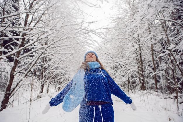 Kobieta w niebieskim dresie, białe rękawiczki i szalik, by rzucić śnieg w zimie w pokrytym śniegiem lesie