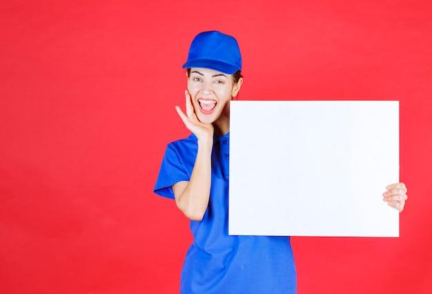 Kobieta w niebieskim mundurze i berecie trzymająca białe kwadratowe biurko informacyjne i pozytywnie nastawiona.