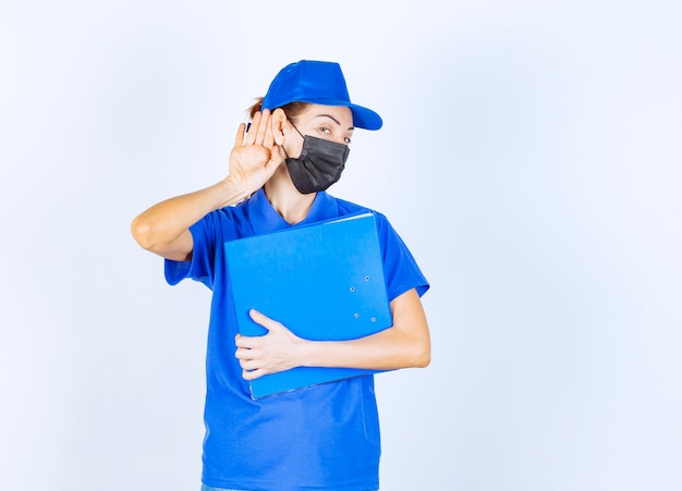 Kobieta w niebieskim mundurze i czarnej masce na twarz trzyma niebieski folder i otwiera ucho, aby dobrze słyszeć.