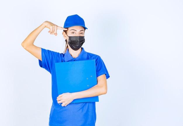 Kobieta w niebieskim mundurze i czarnej masce na twarz trzyma niebieski folder i wygląda na zdezorientowaną i zamyśloną.