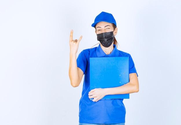 Kobieta w niebieskim mundurze i czarnej masce na twarz trzymająca niebieską teczkę i czująca się pozytywnie i przyjaźnie.