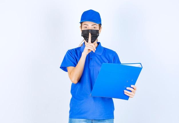 Kobieta w niebieskim mundurze i czarnej masce na twarzy trzymająca niebieską teczkę i prosząca o ciszę.