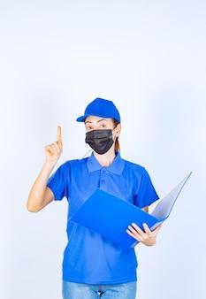 Kobieta w niebieskim mundurze i czarnej masce sprawdzająca raporty i zwracająca uwagę na błąd.