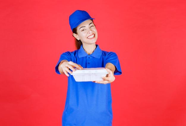 Kobieta w niebieskim mundurze trzyma białe plastikowe pudełko na wynos do dostawy.