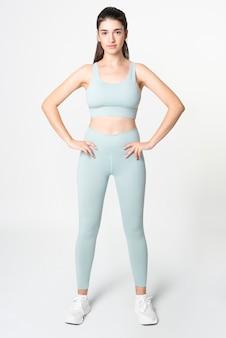 Kobieta w niebieskim sportowym biustonoszu i legginsach