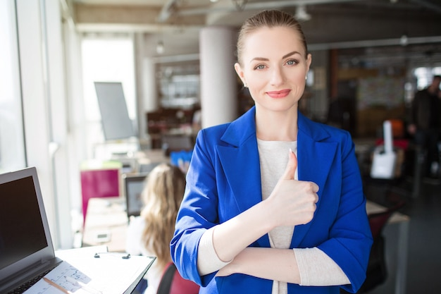 Kobieta w niebieskim stroju uśmiecha się do biura i daje kciuk w górę