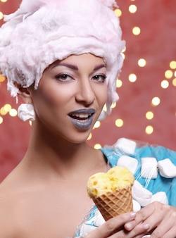 Kobieta w niecodziennej sukience z pianki i peruki z waty cukrowej