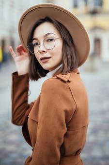 Kobieta w nowoczesnych okularach i moda kapelusz i brązowy płaszcz pozuje w centrum miasta