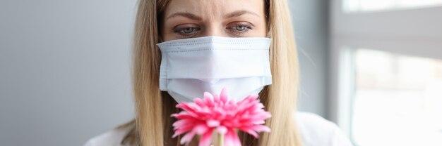 Kobieta w ochronnej masce medycznej wąchająca kwiat