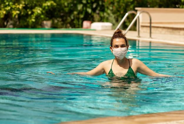 Kobieta w ochronnej masce medycznej z wewnętrznym basenem i pływanie na cyprze koronawirusem covid-19 sezon turystyczny 2021.wakacje