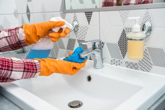 Kobieta w ochronnych rękawiczkach trzymająca spray i szmatkę, wykonująca prace domowe w łazience, czyszczenie kranu.
