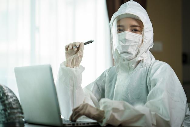 Kobieta w ochronnym hazmat kostiumu pracowniku analizuje w laboratorium w laboranckim komputerze. aby zatrzymać rozprzestrzenianie się koronawirusa lub covid-19.