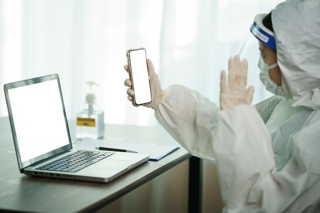 Kobieta w ochronnym hazmat kostiumu pracowniku odpoczywa i wideo dzwoni na mądrze telefonie w laboranckim komputerowym komputerze. aby zatrzymać rozprzestrzenianie się koronawirusa lub covid-19.