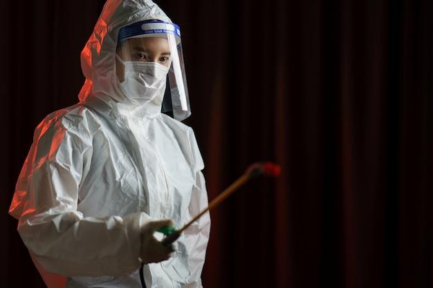 Kobieta w ochronnym kombinezonie przeciwmgielnym rozpylającym środek dezynfekujący, aby zatrzymać rozprzestrzenianie się koronawirusa lub covid-19.