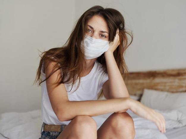 Kobieta w odosobnionym pokoju siedzi na łóżku i ma na twarzy maskę medyczną pandemia samotności