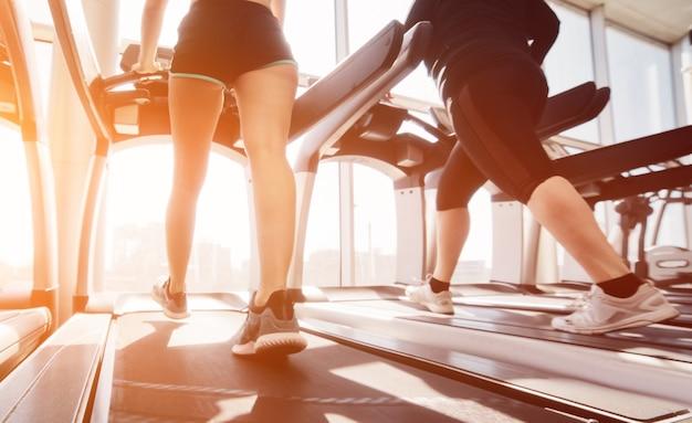 Kobieta w odzieży sportowej i trampkach biegnie na bieżni w siłowni przed oknem