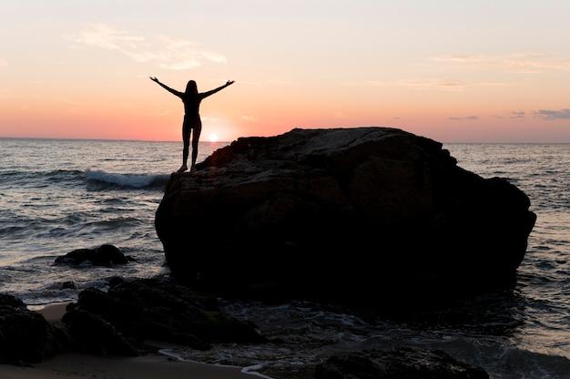 Kobieta w odzieży sportowej, podziwiając zachód słońca z miejsca na kopię