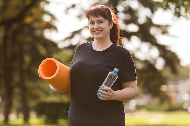 Kobieta w odzieży sportowej, trzymając matę do jogi i butelkę wody