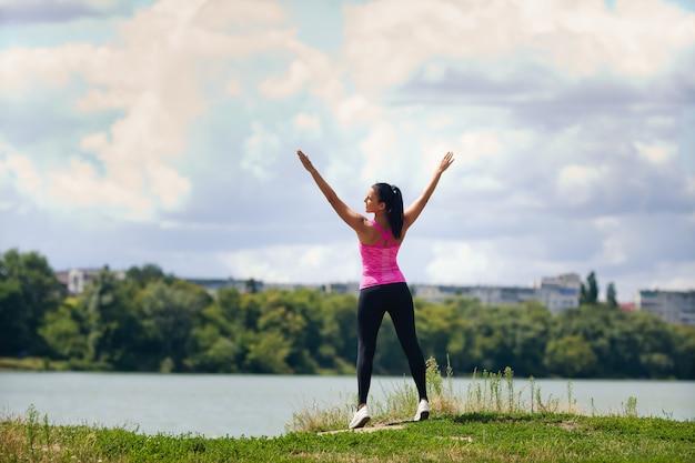 Kobieta w odzieży sportowej uprawia sport na jeziorze w mieście