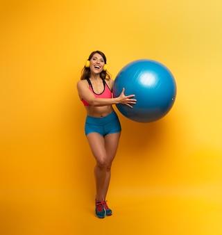 Kobieta w odzieży sportowej z piłką gimnastyczną