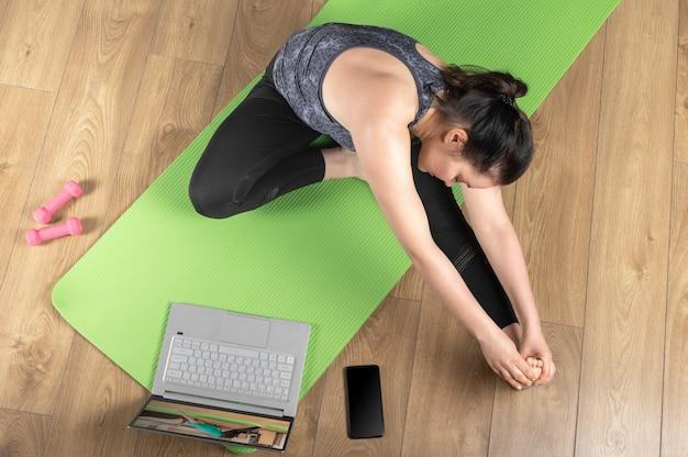 Kobieta w odzieży sportowej zrobić zajęcia jogi na odległość. kobieta robi ćwiczenia fitness, ćwiczenia rozciągające za pomocą laptopa za pośrednictwem połączenia wideo.