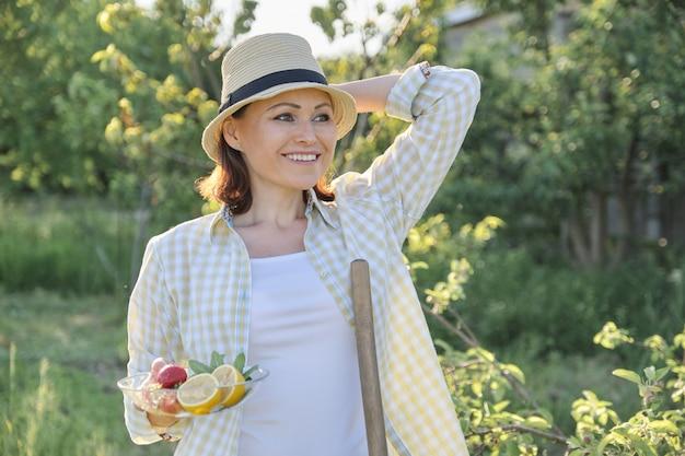 Kobieta w ogrodzie w słomkowym kapeluszu z talerzem truskawek miętowa cytryna