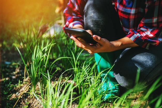 Kobieta w ogródzie z smartphone